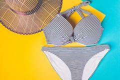 De hoogste mening van twee stukken het gestreepte blauwe en witte zwemmen past en de hoed van het strostrand op blauwe en gele pa Royalty-vrije Stock Fotografie
