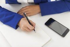 De hoogste mening van vrouw in blauwe blazer neemt nota's bij een lijst Stock Foto