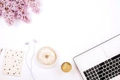 De hoogste mening van vrouwelijke werknemerdesktop met laptop, bloemen en verschillend bureau levert punten Vrouwelijke creatieve stock foto's