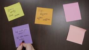 De hoogste mening van vrouwenhanden die op gekleurde kleverige post-it schrijven neemt nota van motievencitaten gebruikend zwarte stock video