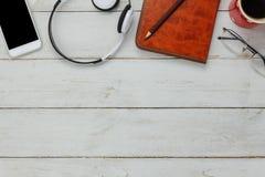 De hoogste mening/Vlak legt het pen/notaboek/witte mobiele telefoon/het luisteren radiomuziek Stock Afbeelding