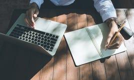 De hoogste menings bedrijfsvrouw schrijft bij notitieboekje en gebruikslaptop werken openlucht in de donkere toon van de koffiewi Stock Fotografie