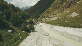 De hoogste rivier van de meningsberg Wandelende groep die langs bergrivier lopen stock video