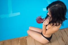De hoogste zitting van de menings donkerbruine vrouw dichtbij de het zwembad en het drinken cocktail op de achtergrond van perfec Royalty-vrije Stock Afbeelding