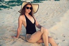 De hoogste zitting van het menings Jonge gelukkige aantrekkelijke meisje op wit zand, die een modieus zwart zwempak en glazen dra stock fotografie
