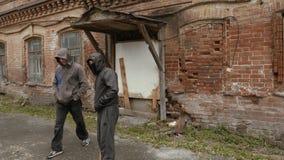 De hooliganmensen in zwart masker met honkbal slaan in misdadig district in stad stock video