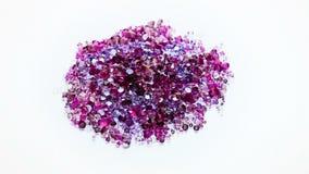 De hoop die van juweelstenen in violette tonen over wit spinnen stock videobeelden