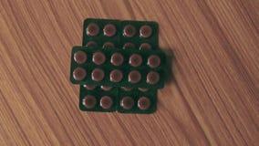 De hoop van Capsules in blaren, ronde worden ingepakt vormde gevormde geneeskundetablet of antibiotische pillen op houten lijstac