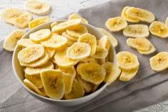 De hoop van droge banaan breekt snack in witte kom op rustieke lijst af stock fotografie