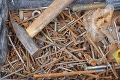 De hoop van oude roestige spijkers en schroeven op bodem van kan met hamer stock foto