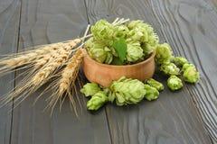 De Hopkegels van bierbrouweningrediënten in houten kom en tarweoren op donkere houten achtergrond Het concept van de bierbrouweri Royalty-vrije Stock Foto's