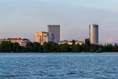 De horizon van Boekarest bij zonsondergang met water en hemel stock foto