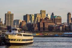 De horizon van Brooklyn bij zonsondergang met boot in mening stock fotografie