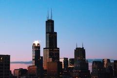 De horizon van Chicago bij schemer met schroeit Toren Stock Afbeeldingen