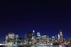 De horizon van de Stad van New York bij de Lichten van de Nacht Stock Foto
