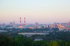 De horizon van een grote stad bij zonsondergang Woonhuizen, industriële pijp Royalty-vrije Stock Afbeelding