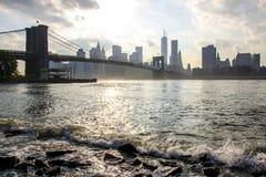 De horizon van Manhattan en de Brug van Brooklyn De riviergolven van het oosten De Stad van New York stock afbeelding
