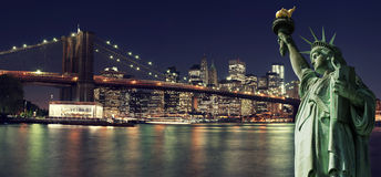 De Horizon van New York bij nacht met Standbeeld van Vrijheid royalty-vrije stock foto's