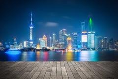 De horizon van Shanghai bij nacht met houten vloer stock foto