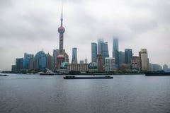 De horizon van Shanghai op een bewolkte die dag met de wolkenkrabbers in wolken en mist worden behandeld stock foto