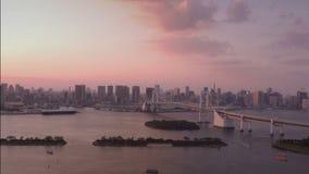 De horizon van Tokyo met de Toren van Tokyo en Regenboogbrug bij zonsondergang in Tokyo, Japan stock footage