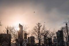 De horizonsilhouet van Chicago met twee vliegtuigen die over de stad vliegen stock fotografie