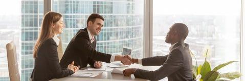 De horizontale beeld Afrikaanse werkgever wenst partner met succesvolle onderhandelingen geluk royalty-vrije stock foto