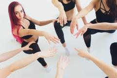 De horizontale dichte omhooggaande meisjes en de kerels van fotojongeren houden hoog vijf gebaarsymbool van stapelhanden samen va stock foto