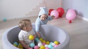 De horloges van de babyjongen zoals een ander vrolijk jong geitje speelt in een pool van kleurrijke bal stock videobeelden