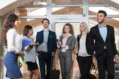 De hotelbeheerder Welcome Business People in Hal, de Gasten van de het Zakenluigroep van het Mengelingsras komt aan Stock Afbeeldingen