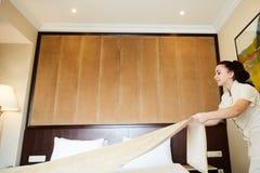 De hoteldienst het vrouwelijke meisje dat van de huishoudenarbeider bed met beddegoed maakt bij herbergenruimte Gemaakt makend be stock fotografie