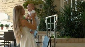De houdende van baby van de moederholding in haar wapens en het kussen van hem Stock Foto