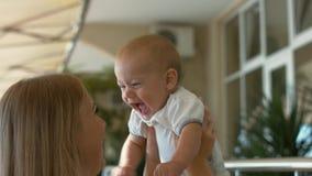 De houdende van baby van de moederholding in haar wapens en het kussen van hem Royalty-vrije Stock Afbeelding