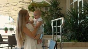 De houdende van baby van de moederholding in haar wapens en het kussen van hem Royalty-vrije Stock Foto