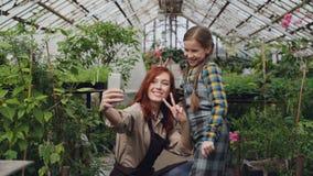 De houdende van moeder en de speelse dochter nemen selfie in serre het stellen, gesturing en maken grappige gezichten Familie stock videobeelden