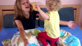 De houdende van moeder heeft pret met leuk dochtermeisje op slaapkamerbed stock footage
