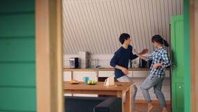 De houdende van paar vrolijke kerel en zijn mooi meisje hebben pret in keuken in het mooie huis ontspannen dansend en stock videobeelden