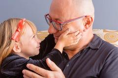 De houdende van vader en de dochter delen een teder ogenblik royalty-vrije stock foto's