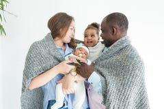 De houdende van vader omvat zijn familie met een plaid Gelukkige multi-etnische familie Familiewaarden royalty-vrije stock foto