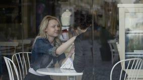 De houdende van vriend die zijn meisje strelen en haar kussen dient een restaurant in genietend van hun datum stock video