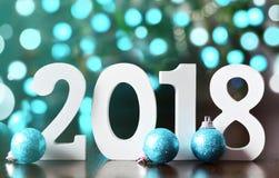 De houten aantallen die het aantal 2018, voor het nieuwe jaar 2018 op vormen schitteren achtergrond Stock Afbeelding