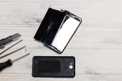 de houten achtergrond op het is gebroken telefoon Gebroken Glas schroevedraaier, mes de reparatieconcept van de celtelefoon stock afbeeldingen