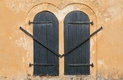 De houten blinden sloten de vensters van de oorspronkelijke vorm, in een huis van koloniale stijl Stock Afbeeldingen