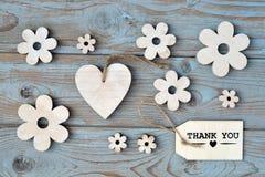 De houten bloemen, hart, zwart schoolbord en danken u etiketteren op een blauwe grijs geknoopte oude houten achtergrond met lege  stock foto