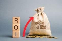De houten blokken met het woord ROI en de omhooggaande pijl met het geld doen in zakken Hoog niveau van bedrijfsrentabiliteit Ren royalty-vrije stock afbeelding
