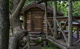 De houten bouw en een gazebo onder bomen Stock Fotografie