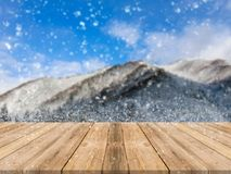 De houten bovenkant van de raads lege lijst van vage sneeuwvalachtergrond Perspectief bruine houten lijst over het blauwe landsch Royalty-vrije Stock Fotografie