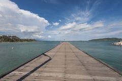 De houten brug over het overzees en de blauwe hemel stock afbeeldingen