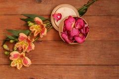 De houten bruine achtergrond met oranje Alstromeria en nam bloemblaadjes toe Stock Afbeeldingen