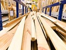 De houten bruine gezaagde natuurlijke de bouw raad plakt logboeken met knopen op een rek op een zaagmolen in de opslag De achterg stock fotografie